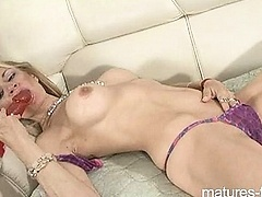 Blonde mature on couch use red dildo